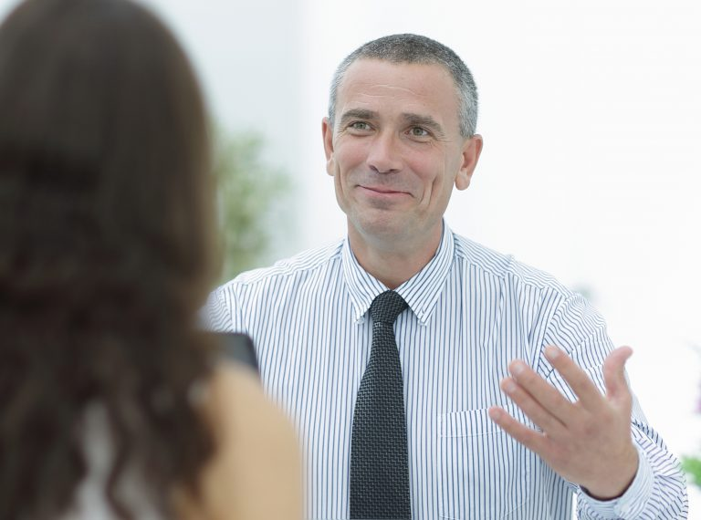 closeup.business consultant sits at his Desk and consult with their client.